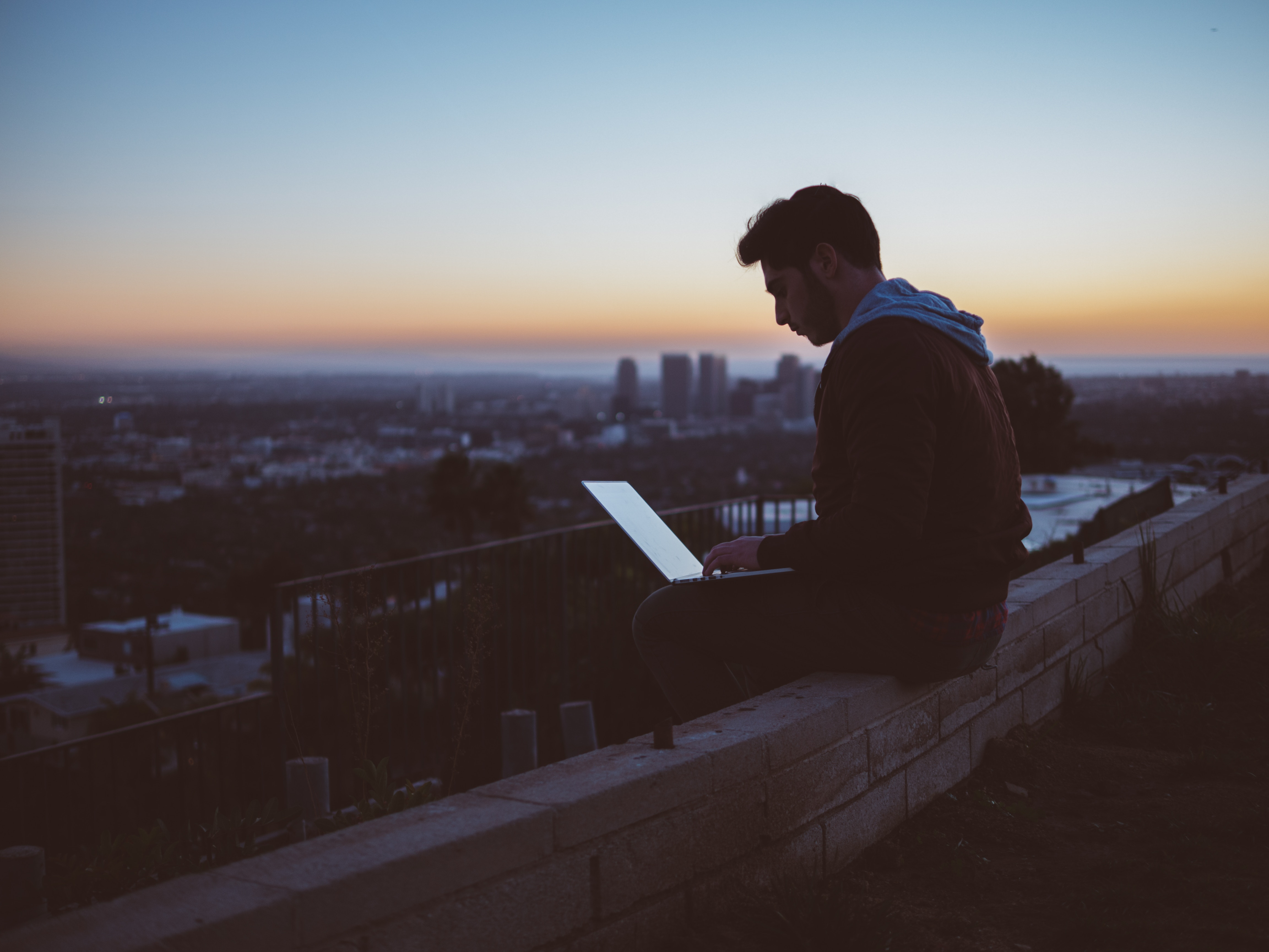 Man Sitting On Ledge Typing